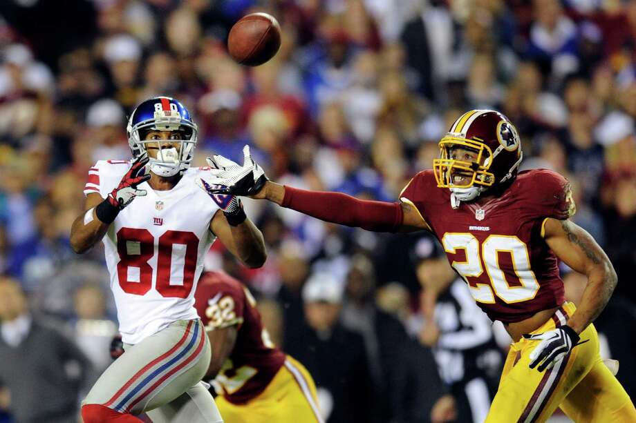 New York Giants wide receiver Victor Cruz (80) pulls in a pass under pressure from Washington Redskins defensive back Cedric Griffin (20) during the first half of an NFL football game in Landover, Md., Monday, Dec. 3, 2012. (AP Photo/Nick Wass) Photo: Nick Wass / FR67404 AP