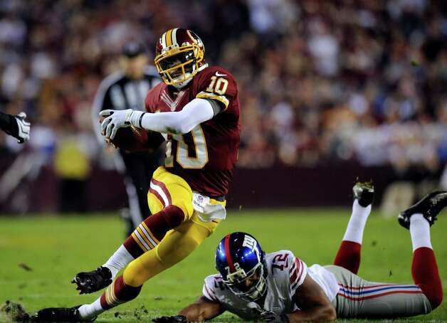LANDOVER, MD - DECEMBER 03:  Quarterback  Robert Griffin III #10 of the Washington Redskins runs with the ball before fumbling the football leading to a touchdown by teammate Josh Morgan #15 in the first quarter against the New York Giants at FedExField on December 3, 2012 in Landover, Maryland.  (Photo by Patrick McDermott/Getty Images) Photo: Patrick McDermott / 2012 Getty Images