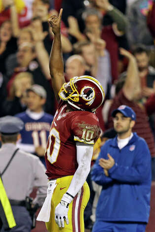 Washington Redskins quarterback Robert Griffin III points skyward after throwing a touchdown pass to wide receiver Pierre Garcon during the second half of an NFL football game against the New York Giants in Landover, Md., Monday, Dec. 3, 2012. (AP Photo/Patrick Semansky) Photo: Patrick Semansky