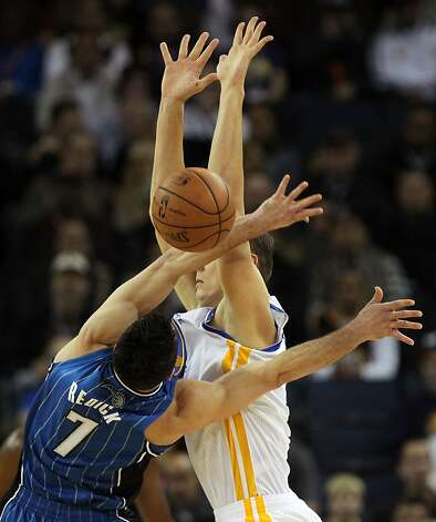 The Warriors' Andris Biedrins and Magic's J.J. Redick make contact in the first half. Redick scored 22 points off the bench. Photo: Lance Iversen, The Chronicle