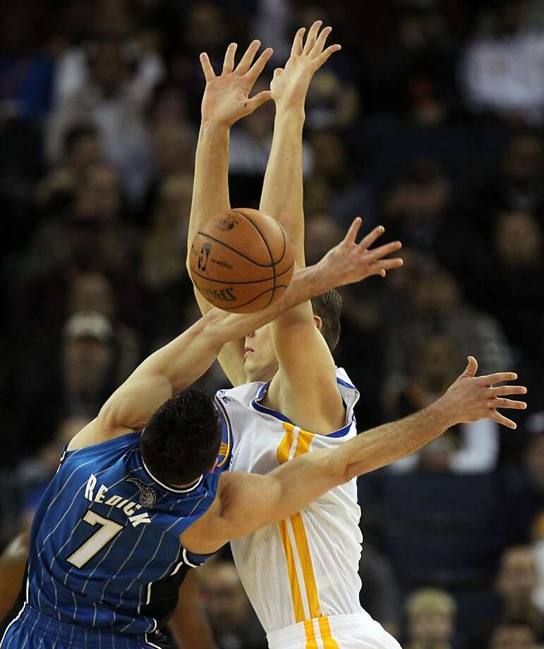 Golden State Warriors' Andris Biedrins (15) battles Orlando Magic's J.J. Redick for the ball during the first half of an NBA basketball game in Oakland, Calif., Monday, Dec. 3, 2012 Photo: Lance Iversen, The Chronicle