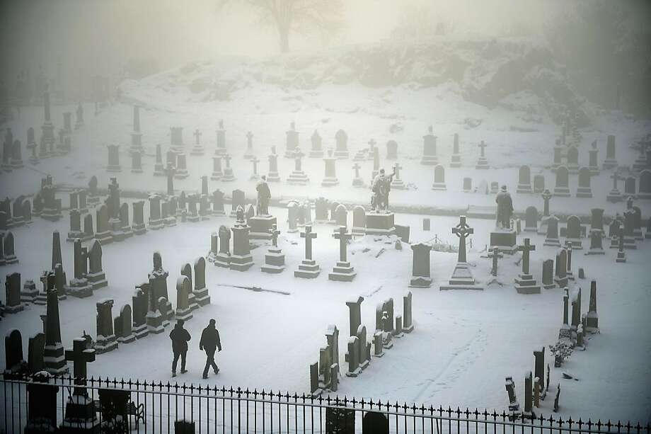 Two men walk through Stirling Castle graveyard on December 3, 2012 in Stirling, Scotland. Snow and sleet has hit many parts of Scotland with heavier falls expected over higher grounds. Photo: Jeff J Mitchell, Getty Images