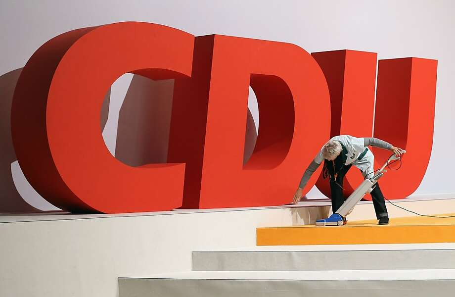 Hoping for a clean sweep:A housekeeper vacuums around the logo of the German Christian Democratic Union, the party of Chancellor Angela Merkel, in Hanover, Germany. The CDU faces federal elections in 2013. Photo: Sean Gallup, Getty Images