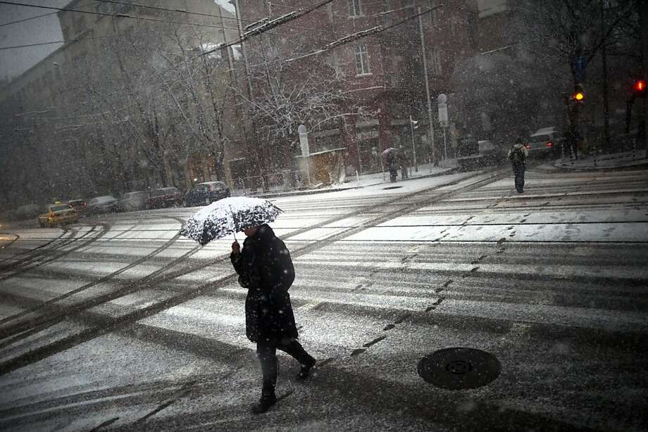 A woman walks with an umbrella as the first snow fall covers Sofia on December 3, 2012. Photo: Dimitar Dilkoff, AFP/Getty Images