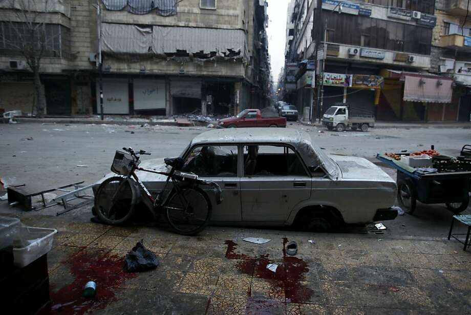 Blood stains are seen on the pavement after artillery mortar shells landed on the opposite side of a bread shop operated by the civilian arm of the Free Syrian Army in the Bustan Al-Qasr neighborhood of Aleppo, on December 3, 2012. The United Nations is to pull non-essential staff out of Syria because of the growing conflict dangers and is restricting travel for those remaining, a UN news agency said. Photo: Javier Manzano, AFP/Getty Images