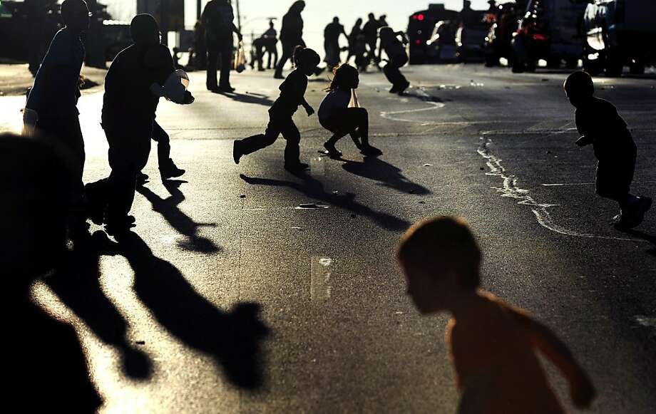 Children scurry around on East Broadway Street in Sweetwater, Texas, to gather candy tossed from the Christmas parade floats on Monday, Dec. 3, 2012. Photo: Joy Lewis, Associated Press