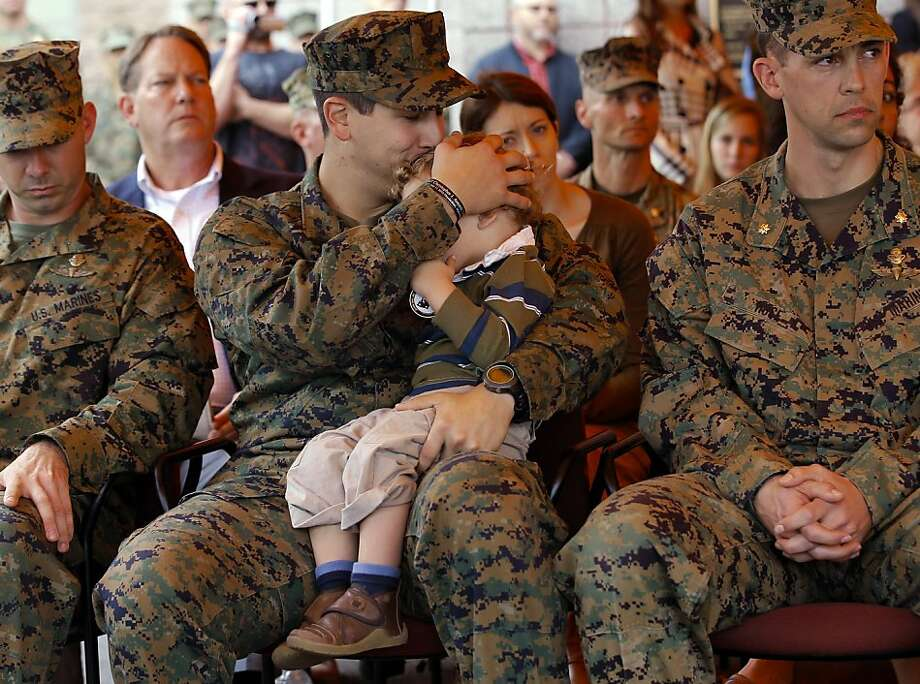 U.S. Navy Petty Officer 2nd Class Patrick Quill, center, kisses his 2-year-old son, Zack, while waiting to receive the Silver Star medal with two other recipients, U.S. Marine Sgt. Frankie Shinost, left, and U.S. Marine Maj. James Rose, right, during a ceremony held at Camp Pendleton, Calif., Monday, Dec. 3, 2012. The three received the medals for their heroism while serving in Afghanistan. Photo: Jae C. Hong, Associated Press