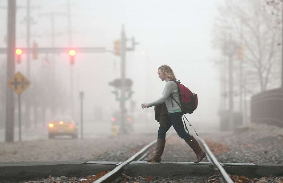 A young woman makes her way toward the Grand Valley State University campus as morning fog changes the landscape in Grand Rapids, Mich., Monday, Dec. 3, 2012. Photo: Chris Clark, Associated Press
