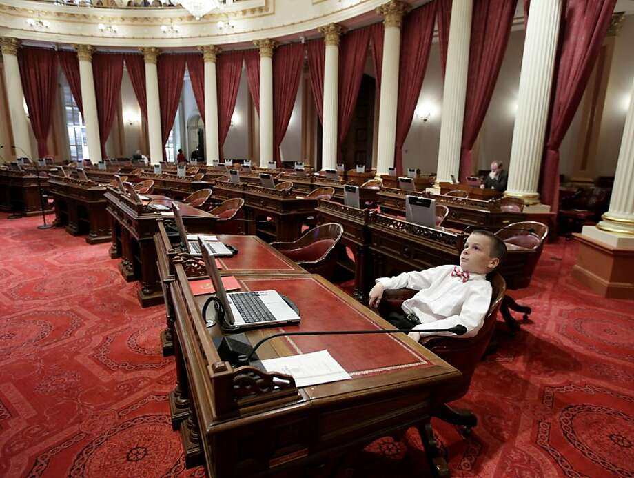 William Knight, 11, relaxes at the desk of his uncle, Sen. Steve Knight, R-Palmdale, before the Senate session at the Capitol in Sacramento, Calif., Monday, Dec. 3, 2012.  Steve Knight , who was elected to the Senate,  after serving in the Assembly, is one of 20 Senators who will take the oath of office Monday.  Both houses of the Legislature meet for the first time since Democrats secured supermajorities in both houses. Photo: Rich Pedroncelli, Associated Press