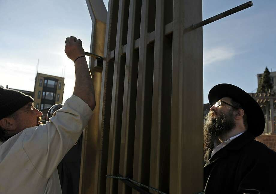 "Rabbi Avrohom Sternberg, right, of Chabad of Eastern Connecticut and Congregation Ahaveth Chesed in New London, braces the structure as James Charland, left, Nate Epperson, center, of Rogovin Moving and Storage, install the menorah on Union Plaza in downtown New London, Conn., Monday, December 3, 2012. the 15-foot tall menorah, which Sternberg estimates weighs well over a ton, will be first lit on the second night of Chanukah this Sunday. ""I've been helping the Rabbi put this thing up for years and I think it's getting heavier,"" said Epperson. Photo: Sean D. Elliot, Associated Press"