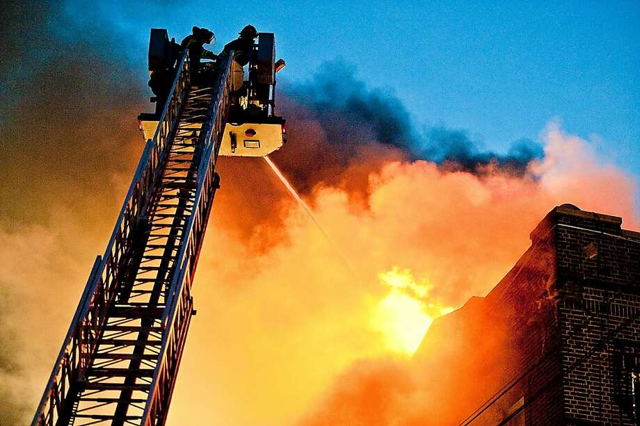 Firefighters work to put out a blaze at Bergenline Avenue and 5th Street in Union City, N.J., on Monday, Dec. 3, 2012. It was not immediately known what caused the fire, which broke out around 3:30 p.m. Monday along Bergenline Avenue in Union City, one of the most densely populated areas of the city in Hudson County. Photo: Lauren Casselberry, Associated Press
