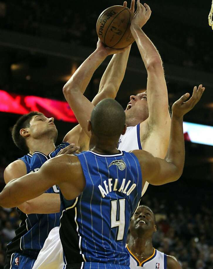 Golden State Warriors' Davis Lee (10) is fauled by Orlando MagicÕ Nikola Vucevic (9) and IArron Afflalo (4) during the second half of an NBA basketball game in Oakland, Calif., Monday, Dec. 3, 2012, Magic won 102-94. Photo: Lance Iversen, The Chronicle