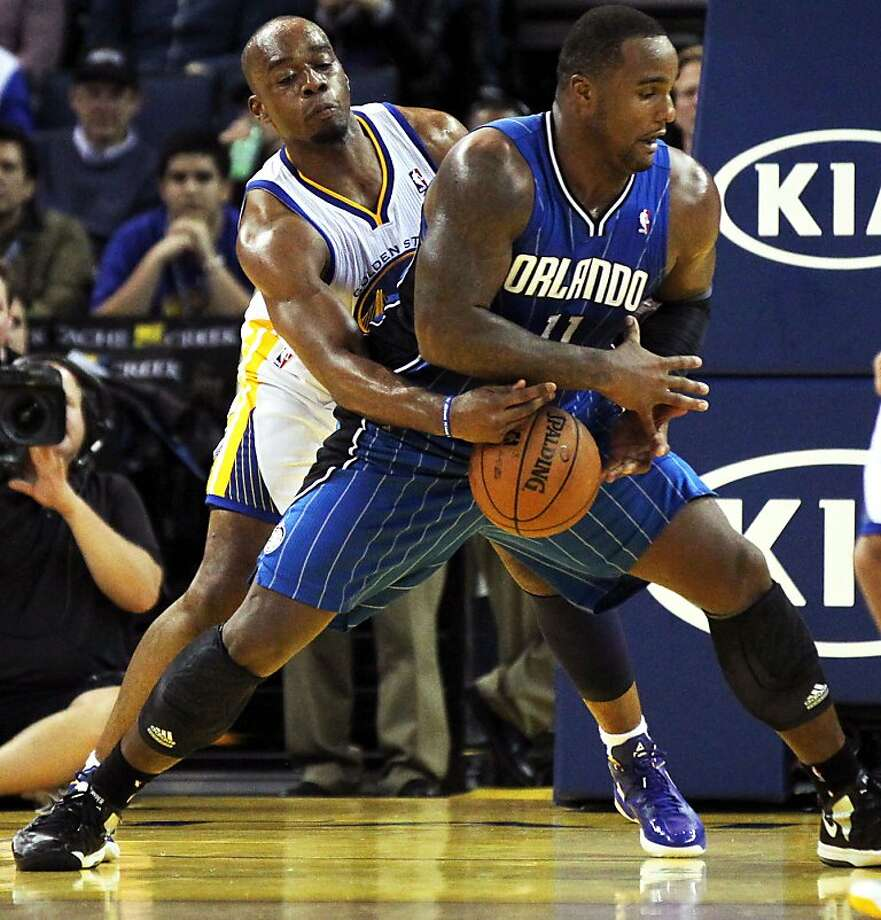 Golden State Warriors' Carl Landry (7) reaches in to take the ball away from Orlando MagicÕ Glen Davis (11) during the second half of an NBA basketball game in Oakland, Calif., Monday, Dec. 3, 2012, Magic won 102-94. Photo: Lance Iversen, The Chronicle