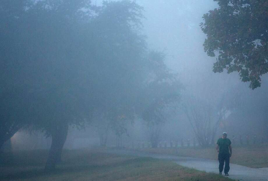 Fog looms as Andres Martinez walks through Stude Park Tuesday, Dec. 4, 2012, in Houston. Martinez said he liked it because it's a change of climate. Photo: Cody Duty, Houston Chronicle / © 2012 Houston Chronicle