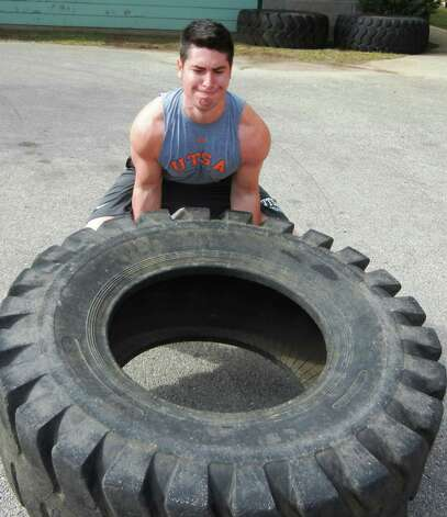 Personal trainer R.J. Delagarza practices his tire-flipping skills at the Braundera YMCA in preparation for the inaugural YMCA Fitness Games, which includes tire-flipping. Courtesy photo Photo: Courtesy Photo