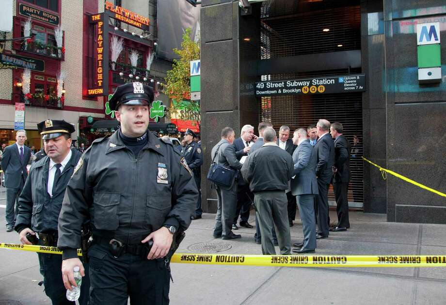 Uniformed and plainclothes police officers stand outside a New York subway station after a man was killed after falling into the path of a train, Monday, Dec. 3, 2012. Photo: Mark Lennihan, Associated Press / AP