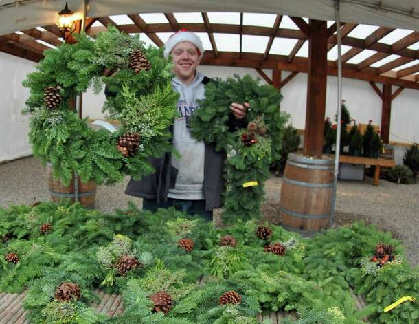 James Shanley of Frogtown Farm in Darien holds up an assortment of wreaths he is selling at the new SoNo Market Place. Christmas trees are also for sale at the marketplace. Photo: Jordan Osterhout/For The Norwalk