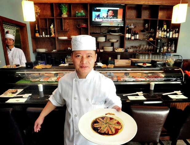 Benny Chow, owner and chef, holds a plate of King Salmon New Style at Ki Asian Bistro & Sushi in Danbury Wednesday, Nov. 21, 2012. Photo: Michael Duffy / The News-Times