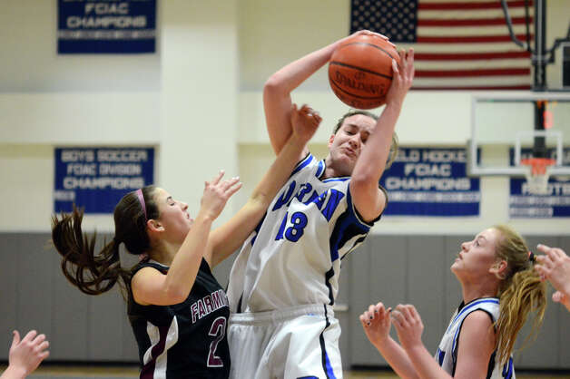 Darien's Kate Bushell (13) grabs a rebound as Farmington's Jamie Bartucca (2) defends during the girls basketball game at Darien High School on Tuesday, Feb. 28, 2012. Photo: Amy Mortensen