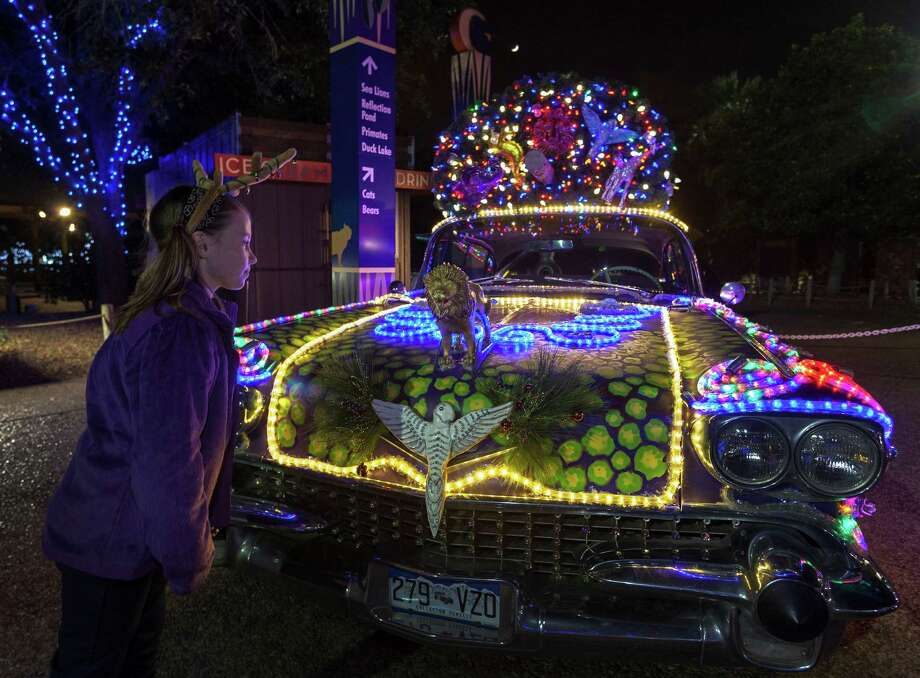 The Houston Zoo, 6200 Hermann Park Drive. Early tour of spectacular Zoo Lights allows its biggest donors a sneak peek of the holiday festival. It opens to the public 6 p.m.-10 p.m., Nov. 23-Jan. 5.  ID: Rachel O'Sullivan, age 10, gets a closer look at the very cool illuminated car near the entrance area.  Friday 11/16/12 (Craig H. Hartley/For the Chronicle) Photo: Craig Hartley, Freelance / Copyright: Craig H. Hartley