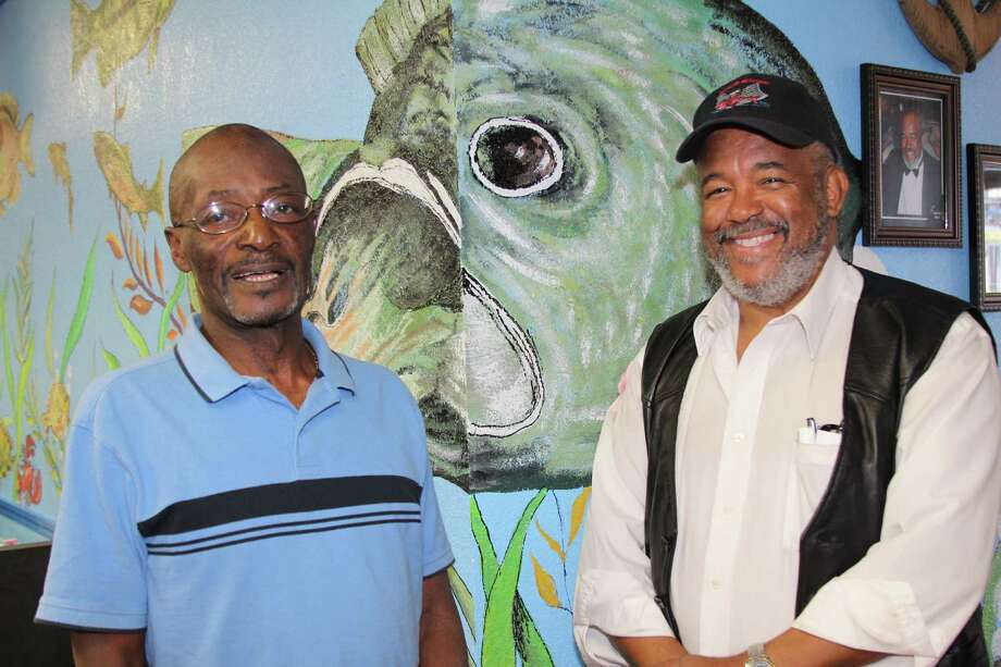 "Artist Glen ""Frank"" Franklin, shown here with franchise owner Derrick Williams (right) has painted sealife murals throughout the Bayseas Seafood and More restaurant. Photo: Lauri Gray Eaton / Northwest Wee"