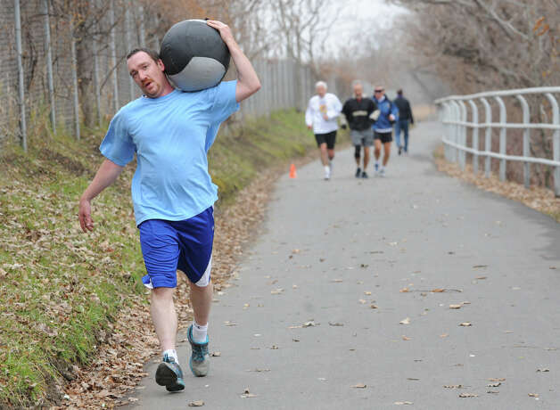 Tom Fitzpatrick of Round Lake runs with a medicine ball on his shoulder down the Corning Trail at the Corning Preserve on Tuesday Dec. 4, 2012 in Albany, N.Y.  Hayes was taking advantage of the nice weather with two friends working out in a cross fit program. (Lori Van Buren / Times Union) Photo: Lori Van Buren