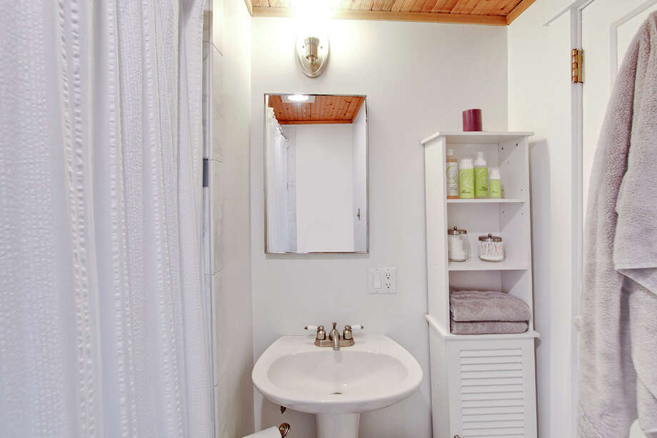 Bathroom of 8530 18th Ave. N.W. The 1,040-square-foot house, built in 1929, has two bedrooms, two bathrooms, a vaulted ceiling in the living room, a loft, a deck and an office on a 4,000-square-foot lot. It's listed for $385,000. Photo: Courtesy Carmen A. Kloth/Windermere Real Estate