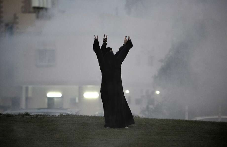 How many fingers am I holding up? Clouds of tear gas fired by riot police swirl around Shiite  protesters following an anti-government demonstration in the village of Abu Saiba, Bahrain. The country's Court of Cessation has set a Jan. 7 date to announce its verdict in the trial of 13 Shiite opposition leaders jailed for their role in last year's unrest. Photo: Mohammed Al-Shaikh, AFP/Getty Images