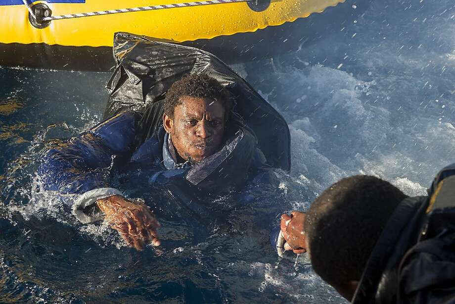 Boat person overboard:Rescuers help a would-be immigrant aboard a Spanish emergency services boat off the Spanish coast. Spanish authorities and the Moroccan navy intercepted three inflatable boats carrying sub-Saharan would-be immigrants across the Strait of Gibraltar. Photo: Marcos Moreno, AFP/Getty Images