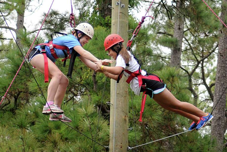 Jersey Village High School students Lauren Pacetti, left, works hard to help Mariam Savarese regain her balance as they work 35 feet above the ground during the Reality Oriented Physical Experience course at Moore Elementary School. Photo: David Hopper, Freelance / freelance