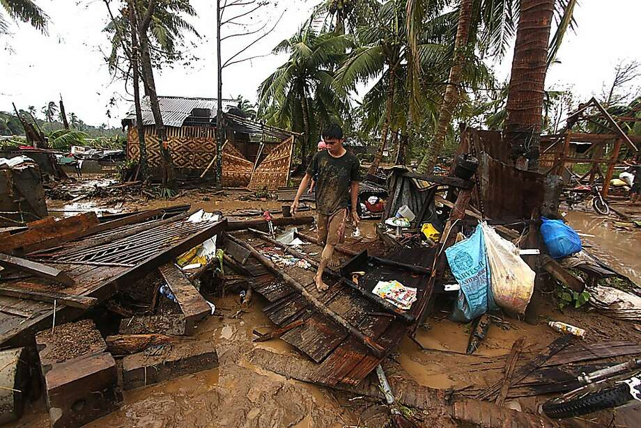Residents walk amid their destroyed houses after Typhoon Bopha wrecked the town of Compostela on the hard-hit southern Philippine island of Mindanao. Photo: Karlos Manlupig, AFP/Getty Images