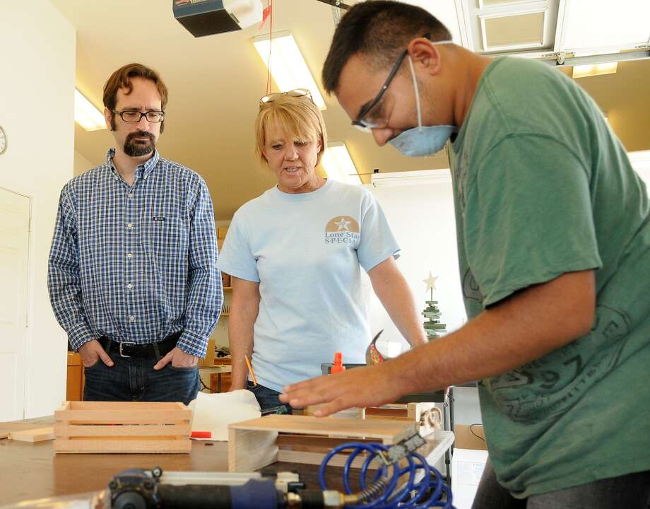 Matt Potter, left, of Simply Texas Gourmet Foods, and New Danville woodshop instructor Sherry Franklin watch as wrangler Alex Macareno builds wooden crates used by Simply Texas for gift packages. Photo: Jerry Baker, Freelance