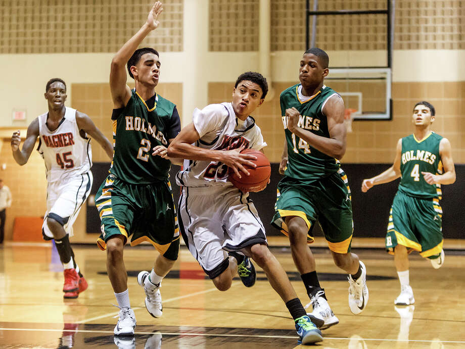 Wagner's Clint Lewis (center) drives the ball upcourt between two Holmes defenders during Wagner's 82-53 win Nov. 29 at Churchill High School, in the opener of the 11th annual North East ISD Invitational Tournament. Photo: MARVIN PFEIFFER, Marvin Pfeiffer / NE Herald / Prime Time Newspapers 2012