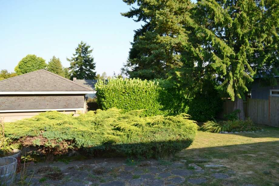Yard of 10324 13th Ave. N.W. The 1,170-square-foot rambler, built in 1949, has three bedrooms, one bathroom, two garages and a patio on a 6,804-square-foot lot. It's listed for $389,000. Photo: Courtesy Leanne Finlay/Windermere Real Estate