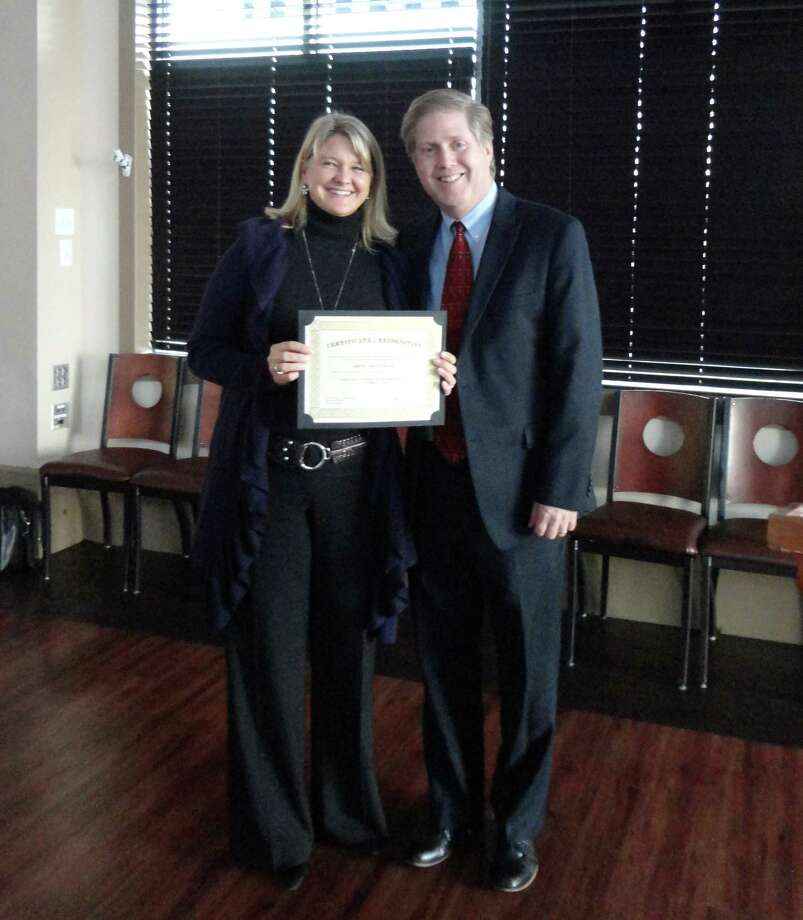 Irene Trautmann displays her certificate from the Connecticut Arts Administrators Association, received for her contributions to music education in Darien. With her is Richard Sadlon, past president of the CAAA and the director of music in the Darien Public Schools. Photo: Contributed