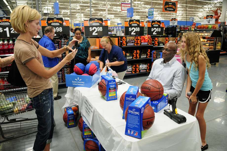 Roxie Vaughn takes a photo of her daughter, Sydnee, 11, a fifth-grader at Sienna Crossing Elementary, with former Houston Rocket and NBA Hall of Famer Clyde Drexler, center, who signed autographs and posed for photos with fans at Wal-Mart Store 5449 at 9929 Texas 6 in Missouri City. The store has sponsored special events since its September opening.  Sydnee was at the store to get Drexler's autograph for her brother Dylan, 8, a third-grader at Sienna Crossing Elementary.   Roxie Vaughn takes a photo of her daughter, Sydnee, 11, a fifth-grader at Sienna Crossing Elementary, with former Houston Rocket and NBA Hall of Famer Clyde Drexler, center, who signed autographs and posed for photos with fans at Wal-Mart Store 5449 at 9929 Texas 6 in Missouri City. The store has sponsored special events since its September opening.  Sydnee was at the store to get Drexler's autograph for her brother Dylan, 8, a third-grader at Sienna Crossing Elementary.   Roxie Vaughn takes a photo of her daughter, Sydnee, 11, a fifth-grader at Sienna Crossing Elementary, with former Houston Rocket and NBA Hall of Famer Clyde Drexler, center, who signed autographs and posed for photos with fans at Wal-Mart Store 5449 at 9929 Texas 6 in Missouri City. The store has sponsored special events since its September opening.  Sydnee was at the store to get Drexler's autograph for her brother Dylan, 8, a third-grader at Sienna Crossing Elementary. Photo: Jerry Baker, Freelance / Greg Krenek