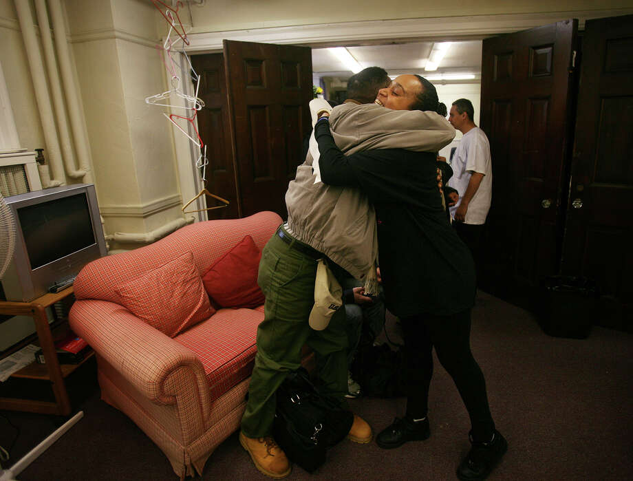 Homeless veteran Rayfield Smith hugs United Way volunteer Monica Jackson, of Bridgeport, at the eighth annual Project Homeless Connect event at the United Congregational Church in Bridgeport on Tuesday, December 4, 2012. The event provides the homeless with access to a wide range of services including medical and dental checks, housing assistance, free haircuts, and warm winter coats. Photo: Brian A. Pounds / Connecticut Post