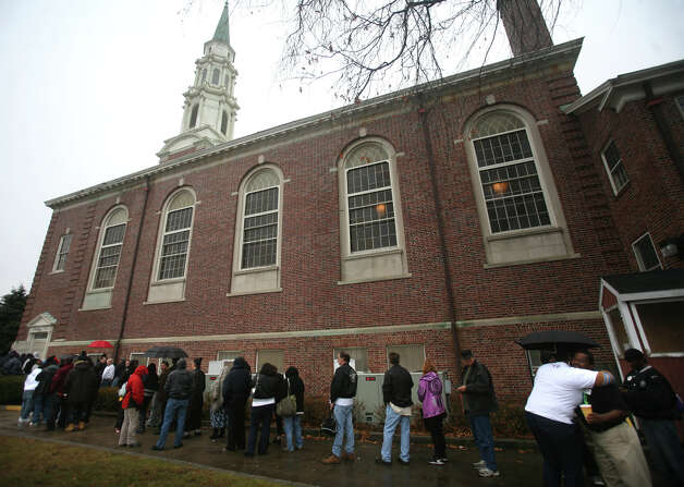 A long line of people wait to be admitted outside the United Congregational Church  for the eighth annual Project Homeless Connect event in Bridgeport on Tuesday, December 4, 2012. Photo: Brian A. Pounds / Connecticut Post