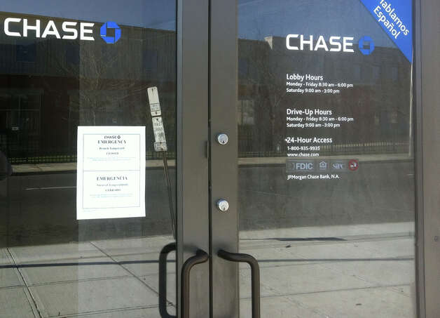 A sign on the door at the Chase bank on State Street in Bridgeport, Conn. notifies customers that the bank is temporarily closed because of an emergency following a robbery on Tuesday, March 27, 2012. Photo: Tom Cleary