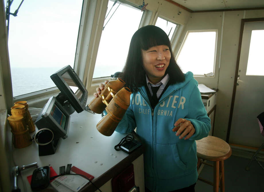 Visiting Korean high school student Kim Sohee rides in the wheelhouse of the Catherine Moore during a visit to  the Aquaculture School in Bridgeport on Tuesday, December 4, 2012. Photo: Brian A. Pounds / Connecticut Post