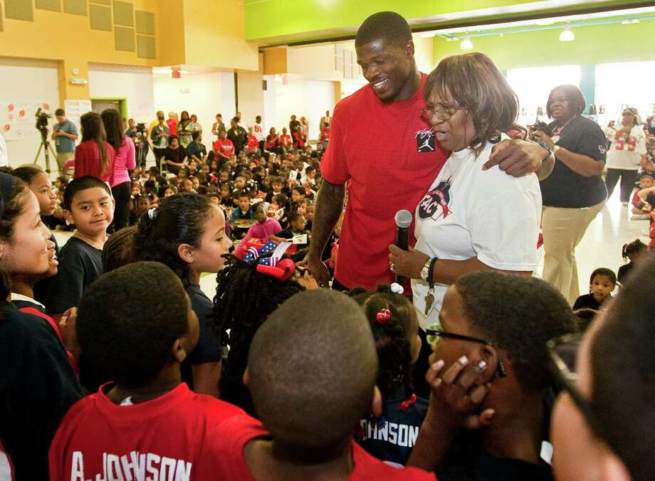 Andre Johnson puts his arm around Jonita Soloman, CEO of GCCSA Head Start, during a Christmas program organized by Houston Police Department's Blue Santa and the Houston Texans' Andre Johnson, Tuesday, Dec. 4, 2012, in Mamie Sue Bastian Elementary in Houston. Johnson called up students wearing a number 80 and gave them gift cards. Photo: Nick De La Torre, Houston Chronicle / © 2012  Houston Chronicle