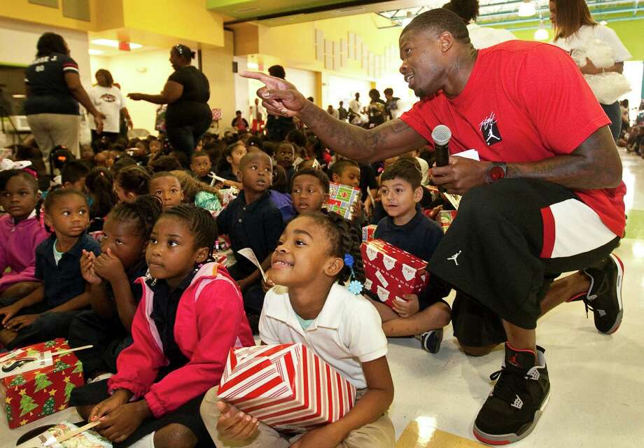 Andre Johnson visits withKiara Bradley, 5, front, and the rest of the kindergarten class during a Christmas program organized by Houston Police Department's Blue Santa and the Houston Texans' Andre Johnson, Tuesday, Dec. 4, 2012, in Mamie Sue Bastian Elementary in Houston. Photo: Nick De La Torre, Houston Chronicle / © 2012  Houston Chronicle
