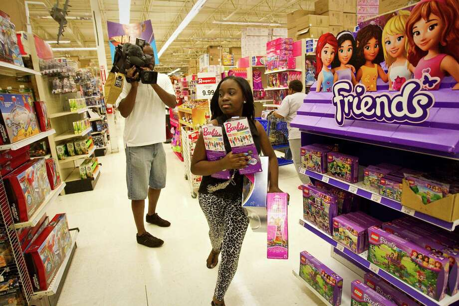 La Rhonda Shaw, 15, hurries to get toys into her cart as she participates in Andre Johnson's 80 second shopping spree for under privileged kids, Tuesday, Dec. 4, 2012, in Toys R Us in Houston. Johnson also bought game consoles and two games for every kid and the total came out to about $19,500. Photo: Nick De La Torre, Houston Chronicle / © 2012  Houston Chronicle