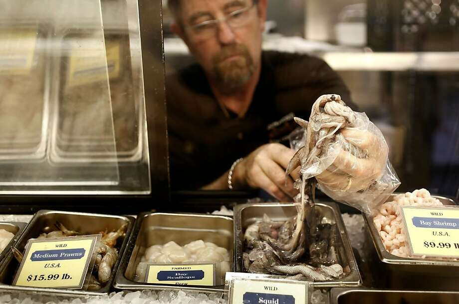 Allen Kuehn, owner of the S.F. Fish Company at the Ferry Building, stocks his last handful of fresh squid. Photo: Michael Macor, The Chronicle