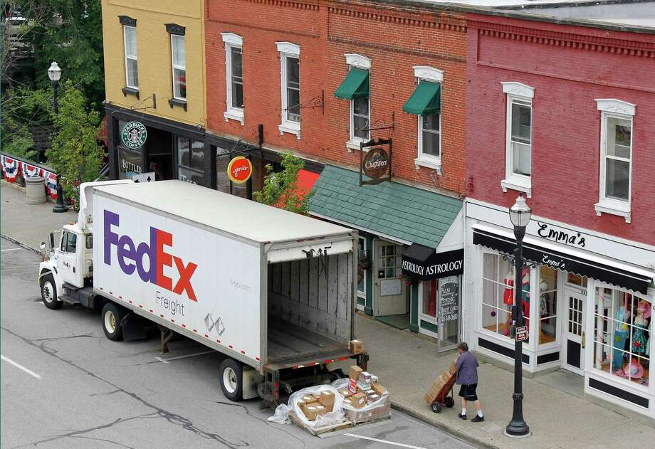 FILE - In this Wednesday, May 23, 2012, file photo, A Federal Express truck makes a delivery in downtown Chagrin Falls, Ohio.  FedEx said Tuesday, Dec. 4, 2012, that it will be offering some employees up to two years' pay to leave the company starting next year. The voluntary program is part of an effort by the world's second-biggest package delivery company to cut annual costs by $1.7 billion within three years. (AP Photo/Amy Sancetta, File) Photo: Amy Sancetta