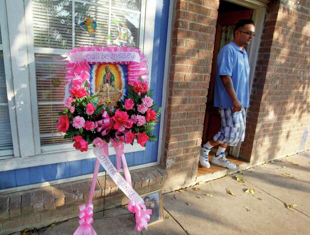Tammy Lydia Ramirez's brother, Joseph Montez, walks past flowers Tuesday Dec. 4, 2012 outside the home where Ramirez was shot, allegedly shot by her boyfriend Jonathan Robert Garcia. Photo: William Luther, San Antonio Express-News / © 2012 San Antonio Express-News