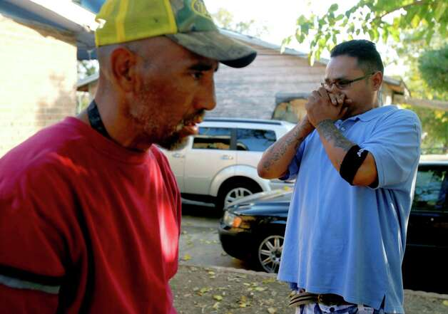 Tammy Lydia Ramirez's father (left) and her brother talk outside the home where she was shot in the yard. Photo: William Luther, San Antonio Express-News / © 2012 San Antonio Express-News