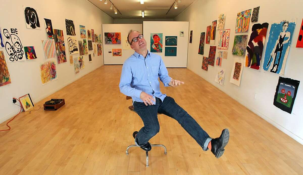 """Tim Buckwalter is the new gallery director at NIAD Art Center plays an air guitar, while promoting the new center, which represents artists with disabilities. Buckwalter has opened a Pop Up Christmas store called """"Holiday Lounge"""" in the storefront of an old auto shop in Richmond. Tuesday Nov. 27, 2012."""
