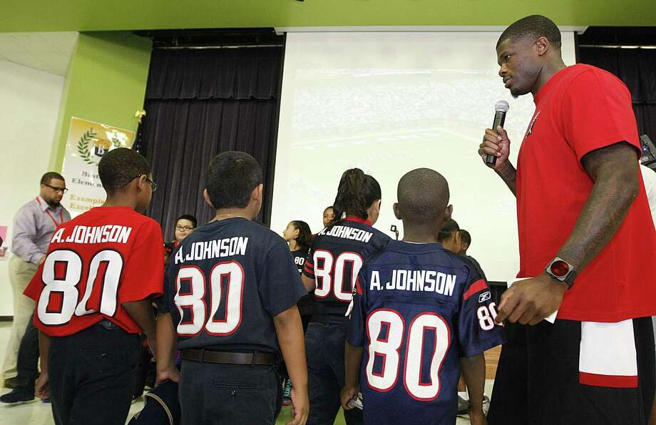 Andre Johnson invites students wearing his number to the stage to give them gift cards during a Christmas event with HPDs Blue Santa at Bastian Elementary. Photo: Nick De La Torre/Houston Chronicle