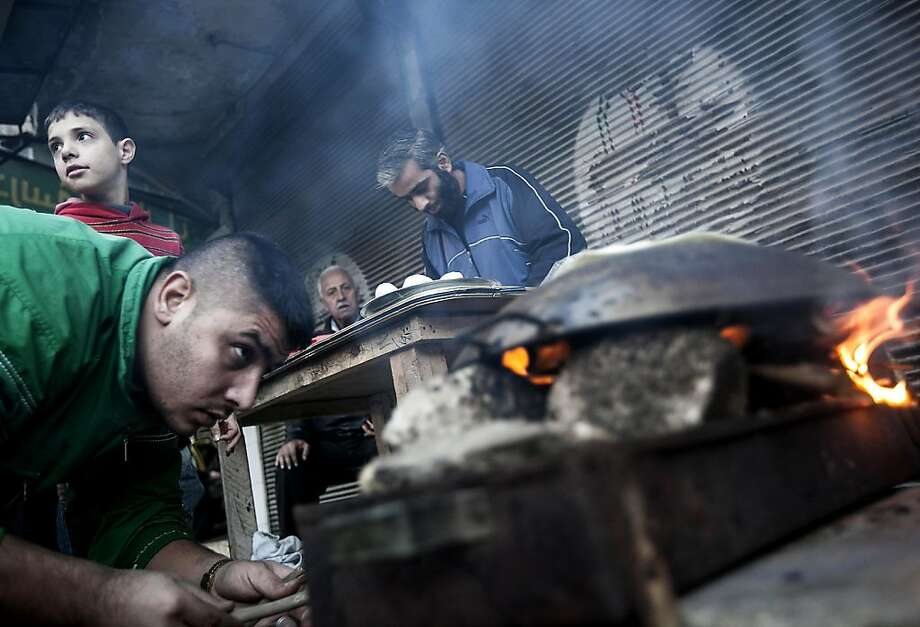 A man bakes bread for residents of Aleppo, Syria's largest city and a key battleground between rebel fighters and government forces. Photo: Narciso Contreras, Associated Press